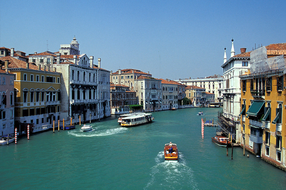 Venice, Italy:  The Grand Canal at midday, as seen from the Ponte dell'Accademia.  Launches such as the one shown in left center transport visitors between the airport and hotels.