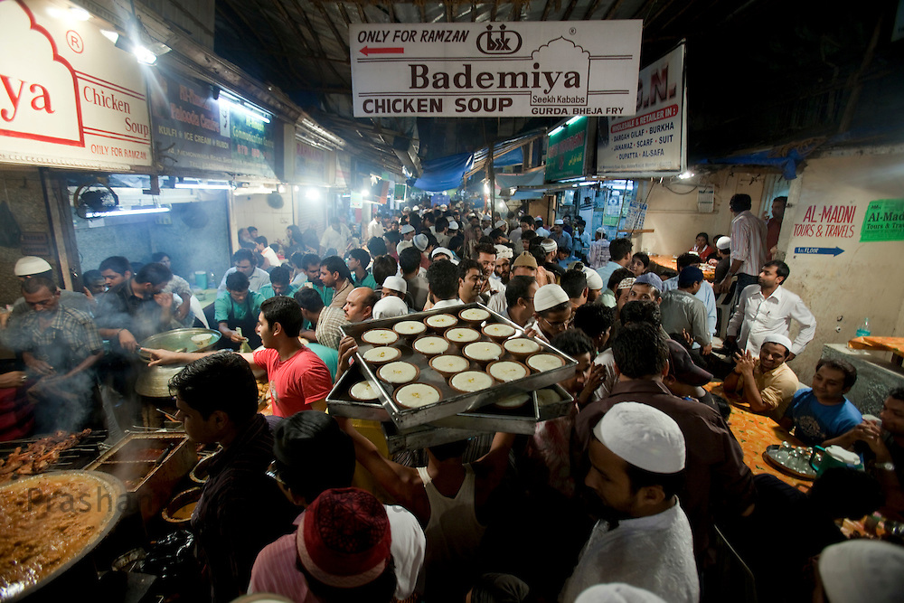 "A man carries ""Firni"" a sweet dish through a crowded lane by Bade Miyan Chicken Soup stall at the enterance of Minara masjid at Mohammed Ali road in Mumbai, Maharashtra, India, on Saturday September 6, 2009. Photographer: Prashanth Vishwanathan/The National"