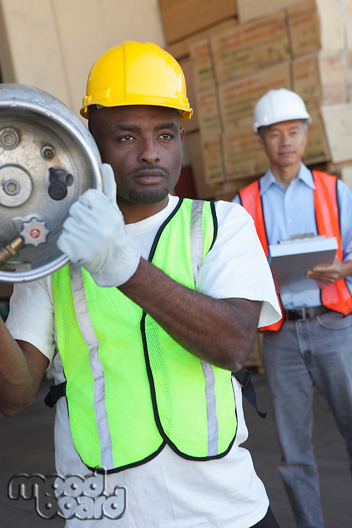Warehouse worker carrying cylinder with manager in background