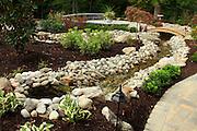 garden scene; flowers; shrubs; patio; running water; small bridge; path; Williamsburg; VA; Virginia