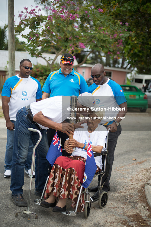 The Queen's Baton carried by Leebert Forbes, and presented to Ms Neil Connor, in Bodden Town, in Cayman Islands, Saturday 12 April 2014. Cayman Islands is nation 55 of 70 nations and territories the Queen's Baton will visit.