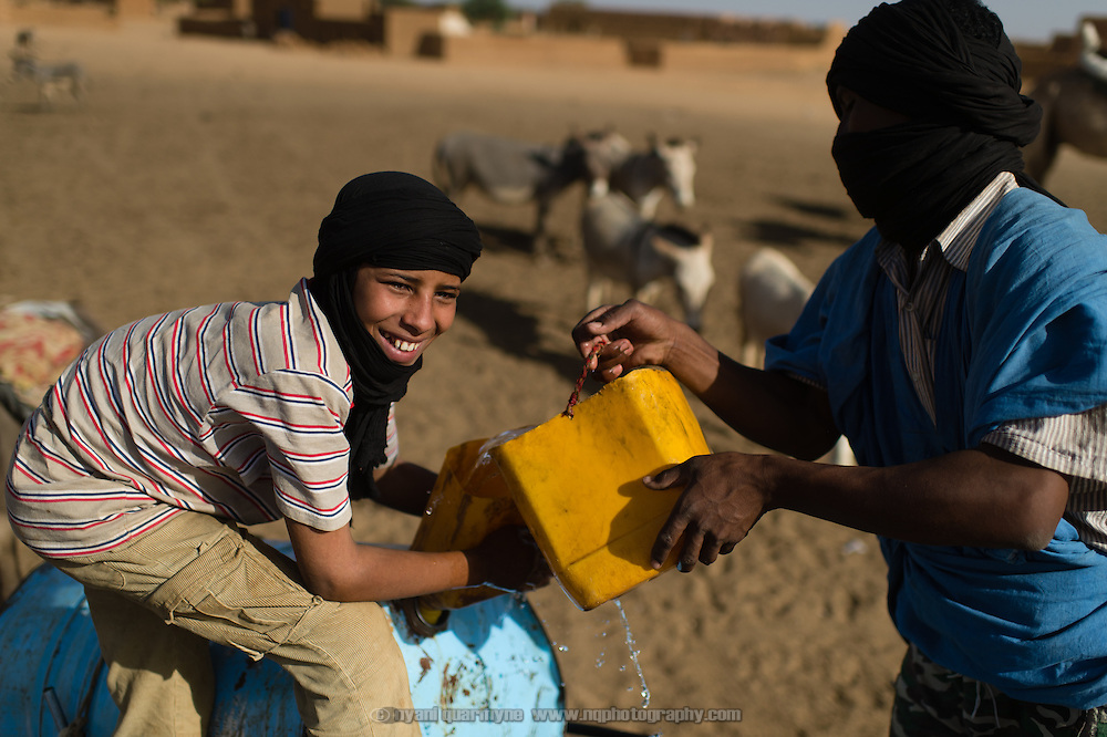 A man and boy filling a barrel of water from an animal trough at a well in Bassikounou, Mauritania on 7 March 2013. According to locals, the town's water supply is non-operational, forcing them to share the well with livestock.