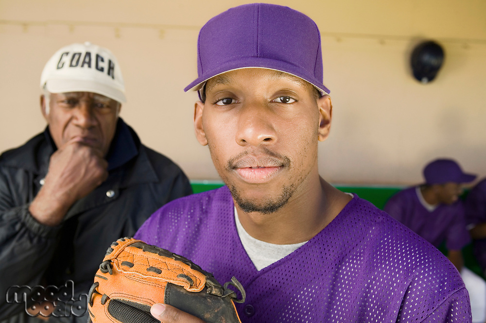 Baseball Player Standing in Dugout with Coach