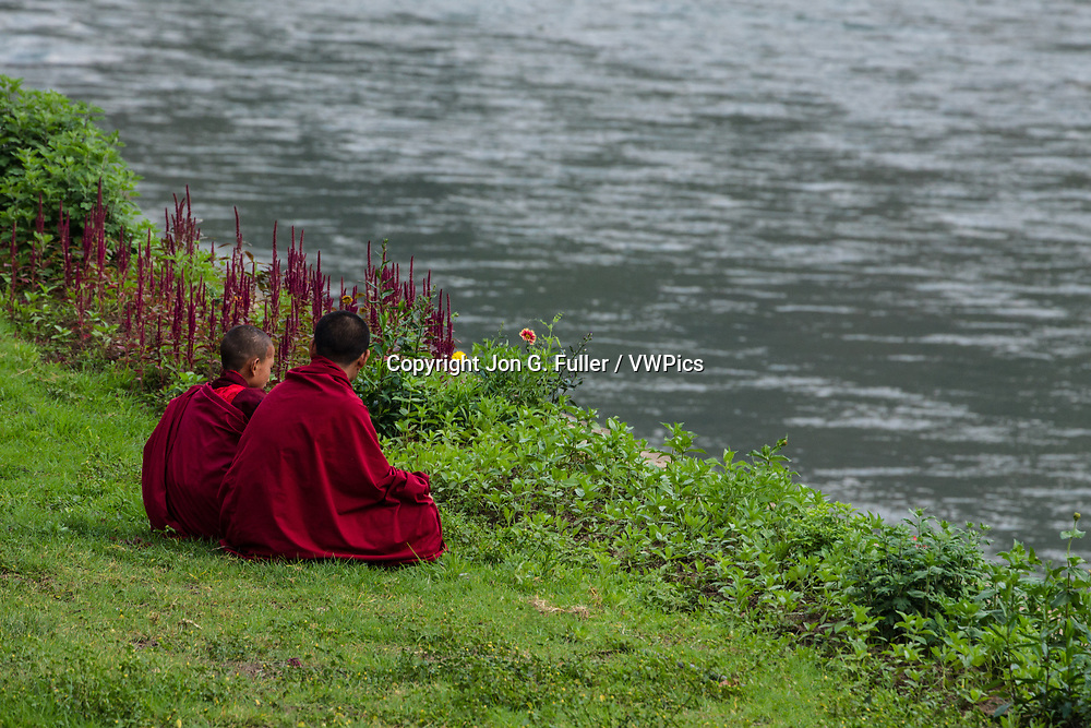 Two young novice Buddhist monks sit in the grass on the bank of the Mo Chhu River at the Punakha Dzong in Punakha, Bhutan.