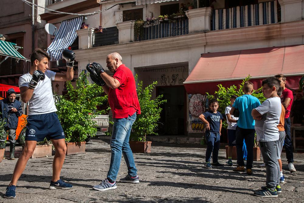 Pino Leto, otto volte campione italiano di boxe ed europeo dei pesi superwelter nel 1989, mentre allena alcuni ragazzi in piazza Caracciolo alla Vucciria di Palermo.