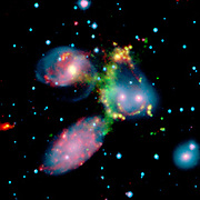 false-colour composite image of the Stephan's Quintet galaxy cluster clearly shows one of the largest shock waves ever seen (green arc). The wave was produced by one galaxy falling toward another at speeds of more than one million miles per hour. The image is made up of data from NASA's Spitzer Space Telescope and a ground-based telescope in Spain. Four of the five galaxies in this picture are involved in a violent collision, which has already stripped most of the hydrogen gas from the interiors of the galaxies. The centres of the galaxies appear as bright yellow-pink knots inside a blue haze of stars, and the galaxy producing all the turmoil, NGC7318b, is the left of two small bright regions in the middle right of the image. One galaxy, the large spiral at the bottom left of the image, is a foreground object and is not associated with the cluster. The titanic shock wave, larger than our own Milky Way galaxy, was detected by the ground-based telescope using visible-light wavelengths. It consists of hot hydrogen gas. As NGC7318b collides with gas spread throughout the cluster, atoms of hydrogen are heated in the shock wave, producing the green glow.