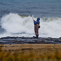 A fisherman fishing in the rough surf while standing on a jetty in Asbury Park NJ>