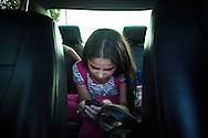 Yuliana Viloria revisa su teléfono móvil en el carro de su madre, Marina Mujica. Gracias a FundaHigado, recibió un trasplante de higado que le permite disfrutar de la vida. Punto Fijo, Venezuela 26 y 27 Oct. 2012. (Foto/ivan gonzalez)
