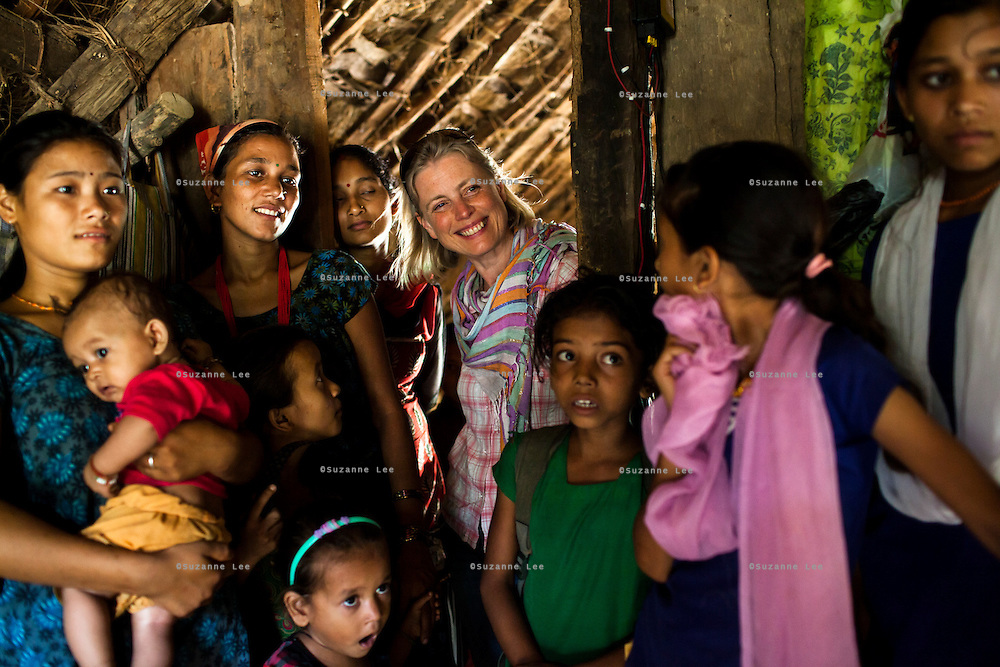 Save the Children UK's Global Director of Media, Ishbel Matheson stands amongst 14 year old Tulasa Khadka's family in their home in the remote village of Dungi Khola, near Chhinchu, Surkhet district, Western Nepal, on 1st July 2012. Tulasa eloped at 13 and gave birth to a stillborn baby weighing less than 1 kg a week ago. She walks through the hills to the nearest hospital and she went into labour while on her way there for a checkup at almost full term. In Surkhet, Save the Children partners with Safer Society, a local NGO which advocates for child rights and against child marriage. Photo by Suzanne Lee for Save The Children UK