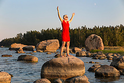 Happy woman standing with outstreched arms on rock in Käsmu beach, Estonia