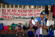 "11 MAY 2013 - BANGKOK, THAILAND:  Speakers use a bullhorn to talk to protesters in front of Government House. Several hundred small scale family farmers camped out ""Government House"" (the office of the Prime Minister) in Bangkok to Thai Prime Minister Yingluck Shinawatra to deliver on her promises to improve the situation of family farmers. The People's Movement for a Just Society (P-move) is a network organization which aims strengthen the voices of different, but related causes working to bring justice for marginalized groups in Thailand, including land rights for small-scale farmers, citizenship for stateless persons, fair compensation for communities forced to relocate to accommodate large scale state projects, and housing solutions for urban slum dwellers, among others.   PHOTO BY JACK KURTZ"