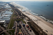"Nederland, Zuid-Holland, Monster, 18-03-2009; Versterking van de kust van Delfland tussen Ter Heijde en Hoek van Holland. De kust bij Ter Heijde, onder in beeld, is een van 'Zwakke Schakels' in de zeewering door de geringe breedte van de duinen. Links van de duinen de Slaperdijk. Richting Hoek van Holland is het strand extra verbreed om een nieuwe duinenrij met duinvallei te maken, natuurcompensatie in verband met de aanleg van de Tweede Maasvlakte. Links achter de duinen de kassen van het Westland, Maasvlakte aan de horizon..Strengthening of the coast of Delfland between Hoek van Holland and Ter Heijde by means of sand-supplementation. This coast is known as one of the ""weak links""  because of the small width of the dunes. In the direction of Hoek van Holland, extra sand has been applied to make an extra dune valley on the beach. This so-called nature compensation is necessary because of the construction of the nearby Maasvlakte 2. To the left and behind the dunes the greenhouses of the Westland area, the Maasvlakte (land reclamation for Port of Rotterdam) at the horizon..Swart collectie, luchtfoto (toeslag); Swart Collection, aerial photo (additional fee required); .foto Siebe Swart / photo Siebe Swart"