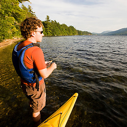 A man fishing next to his kayak on Lake Sunapee at Mount Sunapee State Park in Newbury, New Hampshire.