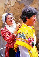 Woman helping to dress a friend at a festival in Provence, France