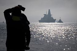 © Licensed to London News Pictures. 02/11/2017. Portsmouth, UK.  A woman watching as HMS Dragon sails into her home port of Portsmouth for the first time in two months.  The Type 45 destroyer has been on a deployment involving exercises with the U.S. Navy and also a visit to the British Overseas Territory of Gibraltar.  Photo credit: Rob Arnold/LNP