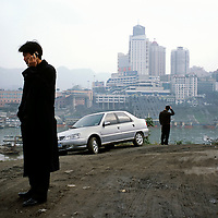Man on his phone at the end of a business meeting, with the city centre behind...From China [sur]real © Mark Henley.......