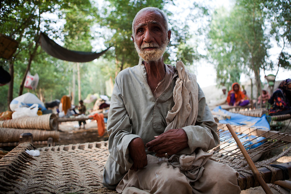 70 year old Amir Bukhash sits on a charpai in a makeshift camp for persons displaced by the extensive flooding in Gujrat Town, district of Muzzafargarh. Partially bind and physically disabled, Amir was rescued by helicopter from his home near Gurat Town...Those fleeing the flooding reported an estimated 200 houses washed away or destroyed by flooding. Most inhabitants of Gujrat earn a living through agriculture, farming Rice, Sugar and Cotton. No deaths were reported by the villagers however they estimate that 90% of the herd of cattle and goats have been lost to flooding. ..Within the makeshift camp children are suffering with diarrhoea and skin complaints. There is no shelter, no sanitation, no access to clean water and no electricity. Most of the IDP's sleep under the trees for shelter from the rain. They complain that they have received very little food and water, and only one one occasion had any access of medical supplies via a private donor...