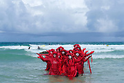 Spectacularly costumed Red Rebels lead a procession of Extinction Rebellion activists across Porthmeor Beach before entering the sea to stand in formation as the rising tide washes over them, symbolising the rise in sea levels caused by climate breakdown on 11th August 2019 in St Ives, United Kingdom. The Red Rebels performance activist troupe dedicated to illuminating the global environmental crisis and supporting groups and organisations fighting to save humanity and all species from mass extinction. Extinction Rebellion is a climate change group started in 2018 and has gained a huge following of people committed to peaceful protests. These protests are highlighting that the government is not doing enough to avoid catastrophic climate change and to demand the government take radical action to save the planet.