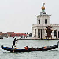 VENICE, ITALY - FEBRUARY 04: A gondola sails on the Grand Canal at Punta della Dogana where amodel of a giant bull - the 2012 edition symbol -has been placed on February 4, 2012 in Venice, Italy. The Carnival of Venice (Carnevale di Venezia) is an annual festival and starts 40 days before Easter and ends on Shrove Tuesday ( Martedì Grasso). (Photo by Marco Secchi/Getty Images)