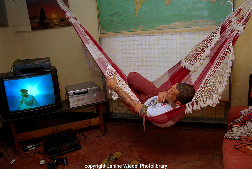 Watching television from hammock strung across room in squat at St Agnes Place Kennington London.