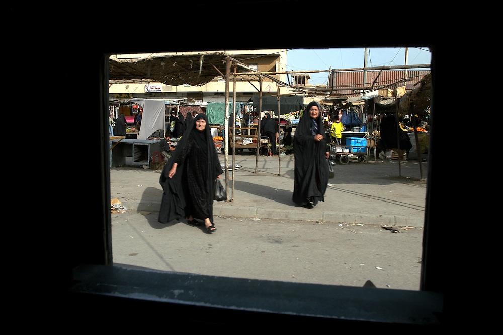 A US army humvee patrol passes Iraqi women in a Sadr City market during a patrol..Baghdad, Iraq. 02/05/2004.Photo © J.B. Russell