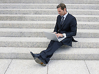 Businessman using laptop on steps