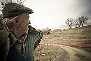 Corleto Perticara (PZ) 17.02.2009, Italy - Tempa Rossa - Speranze e realtà del giacimento Total in Basilicata. In località Petrino, una delle zone interessate dal cantiere, abitavano cinque famiglie, tra cui quella di Zio Antonio, un anziano contadino.  Prima che arrivasse Total a chiedergli i terreni, aveva all'incirca 500 pecore. Ha dovuto cedere all'offerta di Total per l'acquisto di 11 ettari di terreni a circa 6 euro al mq per non incorrere nell'esproprio coatto con il quale avrebbe avuto pagati i terreni a circa 2,50 euro al mq. L'area pascolo si è ridotta ed ha dovuto togliere gli animali rimanendo con circa 25 pecore. NELLA FOTO: Zio Antonio, indica i suoi terreni dove ora c'è il cantiere Total.