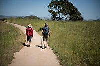 Mike and Diana Ellis hike a trail in Helen Putnam Regional Park on a summer day in Petaluma, California.