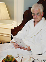 Man sitting on bed reading document