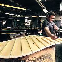 A technician at work on the sound board of a Steinway Piano at the Steinway Factory, Astoria, Queens, New York.