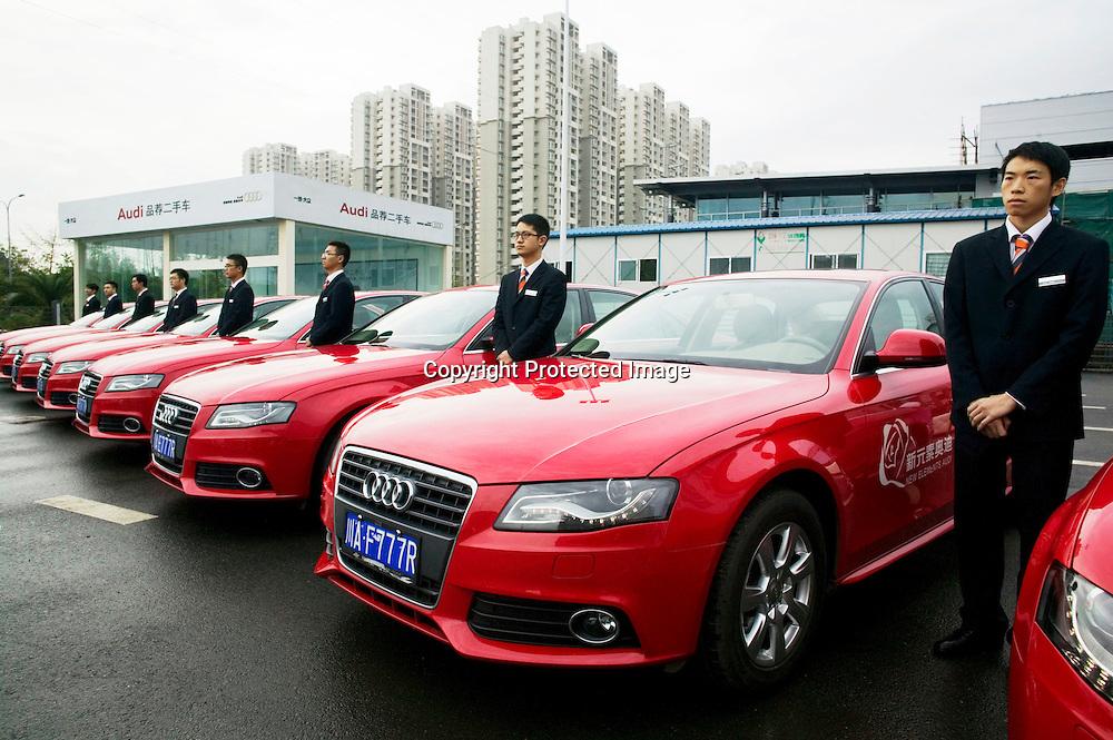 CHENGDU,SICHUAN, OCT. 13.2011 : Audi Angestellte stehen am Eingang der Dealership in Chengdu . Der Audi Vertrieb in Chengdu ist einer der erfolgreichsten auf der Welt.