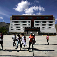 "LHASA, JUNE-16, 2009 : students wak in front of the Tibetan university that is also nicknamed "" little Potala "" due to it's design."