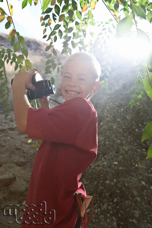 Boy (7-9) using binoculars