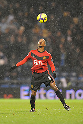 Patrice Evra of Manchester United controls the ball with his head in heavy rain. Portsmouth v Manchester United (1-4), Barclays Premier League Fratton Park, Portsmouth, 28th November 2009.