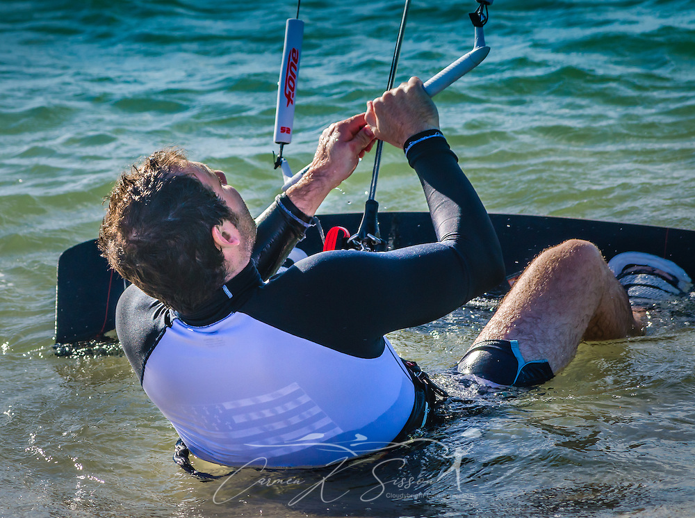 Mathieu Junco leans back in his harness and positions his feet on his kiteboard as he launches  his F-One Bandit Six kite, October 18, 2015, in Dauphin Island, Alabama. Junco, from France, began kitesurfing five years ago. Windy conditions on the island brought surfers out in droves, but many, like Junco, found that the brisk northerly winds made kitesurfing challenging on the south side of the island. Kitesurfing began in France in the 1980's and became a mainstream water sport in 1999, combining aspects of wakeboarding, windsurfing, surfing, and paragliding. More than 1.5 million people participate in the global sport. (Photo by Carmen K. Sisson/Cloudybright)