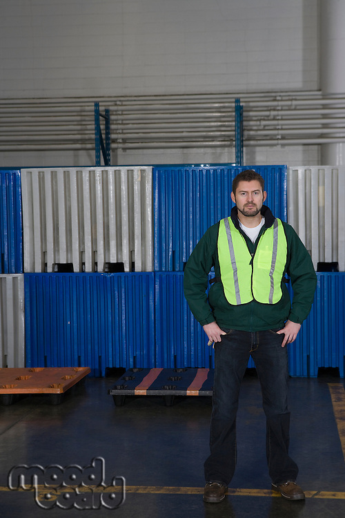 Man standing in factory hands on hips