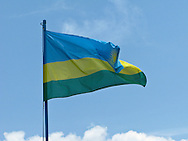 The Rwandan flag flutters in the breeze against the sky.