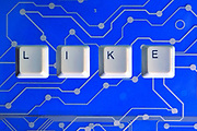 Keyboard keys form the word LIKE on blue electric circuit in the background.