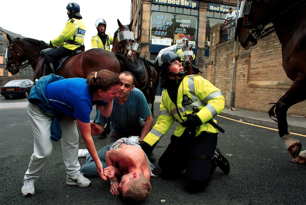 A white man lies injured after being stabbed in the back during disturbances in Bradford city centre. A planned march by The National Front in Bradford today was banned by the police but local Asians and groups of white men still clashed throughout the afternoon. Shops, pubs and cars were also damaged.