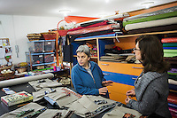 CASERTA, ITALY - 25 FEBRUARY 2015: Sister Rita Giaretta (center), founder of Casa Rut and of the New Hope tailor's shop, talks to volunteers at the tailoring studio in Caserta, Italy, on February 25th 2015.<br /> <br /> New Hope is an ethnic tailor's shop that makes a variety of colourful products working mainly african fabrics. The New Hope social cooperative, founded in 2014, promotes a training workshop for your immigrant women, many of which have children, that want to integrate in Italian society.
