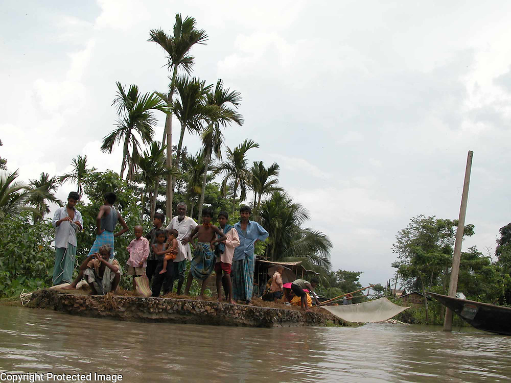 THE PEOPLE ARE STANDING ON A ERODED ROAD WHICH IS ERODED BY FLOOD WATER AND SNAPPED THE LINK BETWWEN ASSAM AND MEGHALAYA STATES IN NORTH EAST INDIA AT FAKIRGANJ village, about 385 kilometers  southwest of Gauhati, capital of northeastern Indian state of Assam, Friday, July 11, 2003. Floods and mudslides in the northeastern states of Assam has killed at least 28 people over the past week and uprooted more than 500,000 from their homes, while 25 lakhs render homeless. (AP Photo/Shib Shankar Chatterjee)