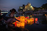 JAPAN, Hiroshima : Paper lanterns float in the Motoyasu River in front of the Atomic Bomb Dome (background) in Hiroshima on August 6, 2015. Tens of thousands gathered for peace ceremonies in Hiroshima on August 6 on the 70th anniversary of the atomic bombing that helped end World War II, but still divides opinion today over whether the total destruction it caused was justified