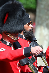 © Licensed to London News Pictures. 09/06/2018. London, UK. Guardsman Charanpreet Singh Lall (C), the first to wear a black turban instead of a bearskin during Trooping the Colour, parades down The Mall as Royal fans wait to see members of the Royal family attend the Trooping The Colour ceremony in London to mark the 92nd birthday of Queen Elizabeth II, Britain's longest reigning monarch. Photo credit: Rob Pinney/LNP