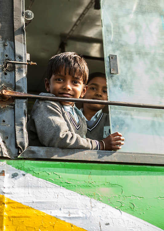 A boy in the open window of a school bus, Delhi, India.