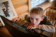 Drake Shannon, 11, one the three children of John Daniel Shannon, 48, a former US Army Senior Sniper, is playing online games on a laptop inside his family home in Westcliffe, CO, USA. Daniel retired here with his family after a serious brain injury inflicted by an insurgent sniper in Ramadi, Al Anbar Province, Iraq, on November 13th 2004. He fought during the Second Battle of Fallujah and was then moved to nearby Ramadi. Daniel lost his left eye and has multiple health issues because of his injury: memory problems, balance problems, he can't smell and taste well anymore, he suffers from PTSD, has  troubles with large crowds and city surroundings. This is the reason why he and his family moved to a quiet location on the Rocky Mountains. In 2007 Dan helped the Washington Post to uncover patients' neglect at the Walter Reed Army Medical Center; he also testified before Congress. Torrey, 42, his wife, is a freelance writer and a contributor for the Huffington Post; she's also campaigning to improve the situation of veterans' families.