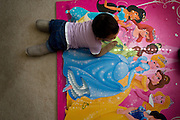 Malyia moves around in her bedroom, stopping to look at the princess on her play mat.