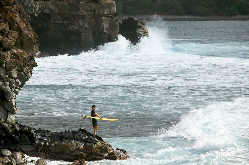 Surfer contemplating surf at Honulua Bay, Maui.  Getting ready to jump off rocks into water.  Framed by Honolua Bay cliffs.