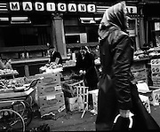 Moore Street, Dublin.      (J97)..1975..23.12.1975..12.23.1975..23rd December 1975..For well over a hundred years Moore Street has served the citizens of Dublin. The longest running open air fruit and vegatable market offers value for money,particularly to those where money is in short supply. Predominately a fruit and veg market there are several traders who sell fish and seasonal goods, as illustrated by the photographs showing turkeys and holly wreaths being sold on the run up to Christmas..Outside the famous Madigans bar this dealer is pictured preparing bunches of mistletoe for Christmas.