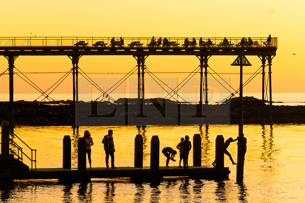 ©Licensed to London News Pictures. 18/09/2019 Aberystwyth UK. <br /> The sun setting gloriously over  Cardigan Bay silhouettes people on the seaside piers at the end of a day of unbroken clear blue skies and warm September sunshine in Aberystwyth ,  as the 'indian summer' mini heat-wave continues over much of the souther parts of the UK. Photo credit Keith Morris/LNP