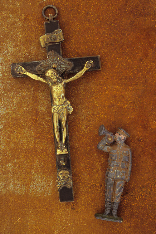 Ebony and brass crucifix lying on rusty metal sheet with worn lead model of World War 1 army bugler at Christs feet